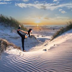 Wanddeko Yoga Asana der Taenzer am Meer magische Yogapraxis mit Sonne in Duenenlandschaft